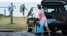 Nominated driver car insurance tile car at beach with boot open parent carrying bag