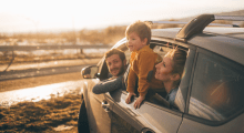 Comprehensive car insurance tile child and parent leaning out of car window