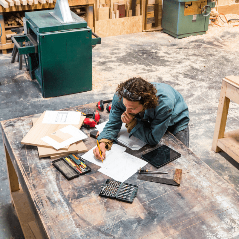 Man standing over a workbench