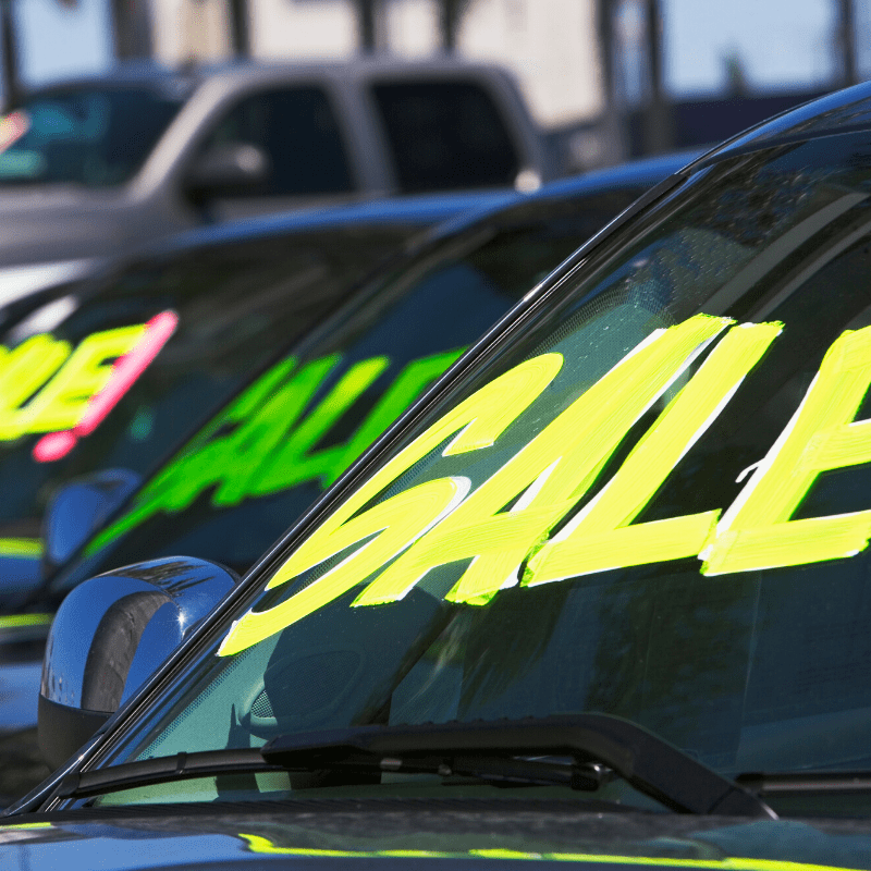 Cars with 'Sale' written in marker on windshields