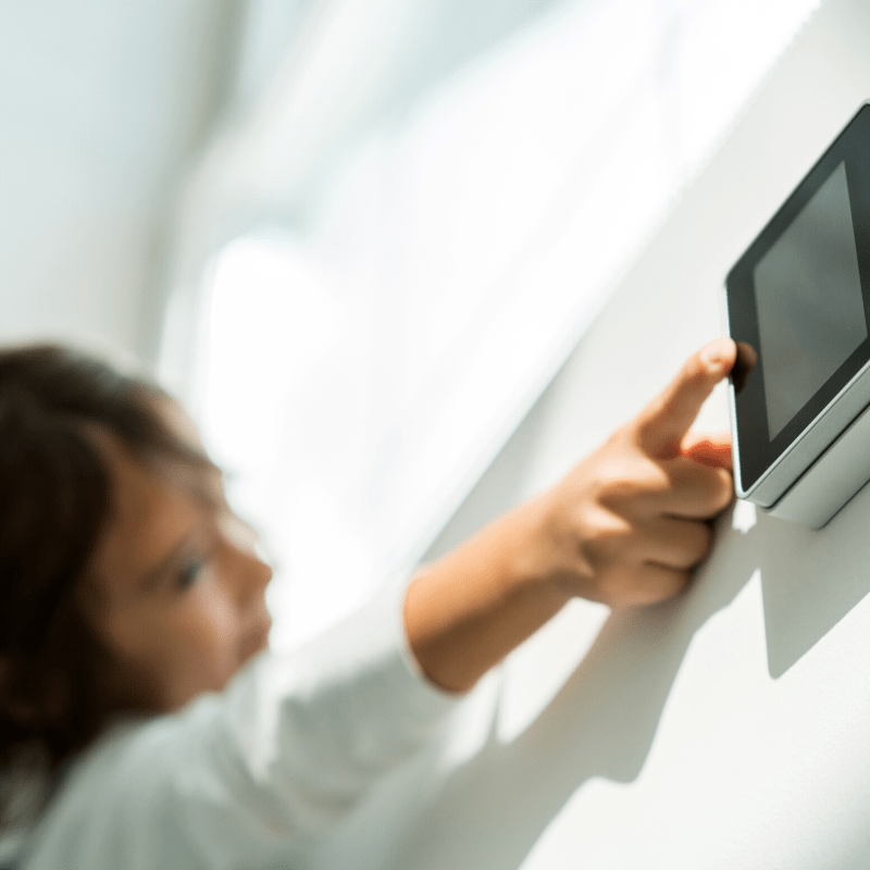 Young child reaching to touch a smart home device on the wall in her home