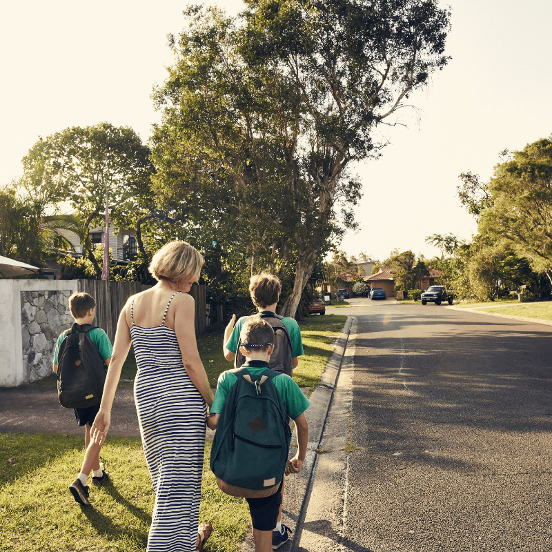 A mother walking three boys to school