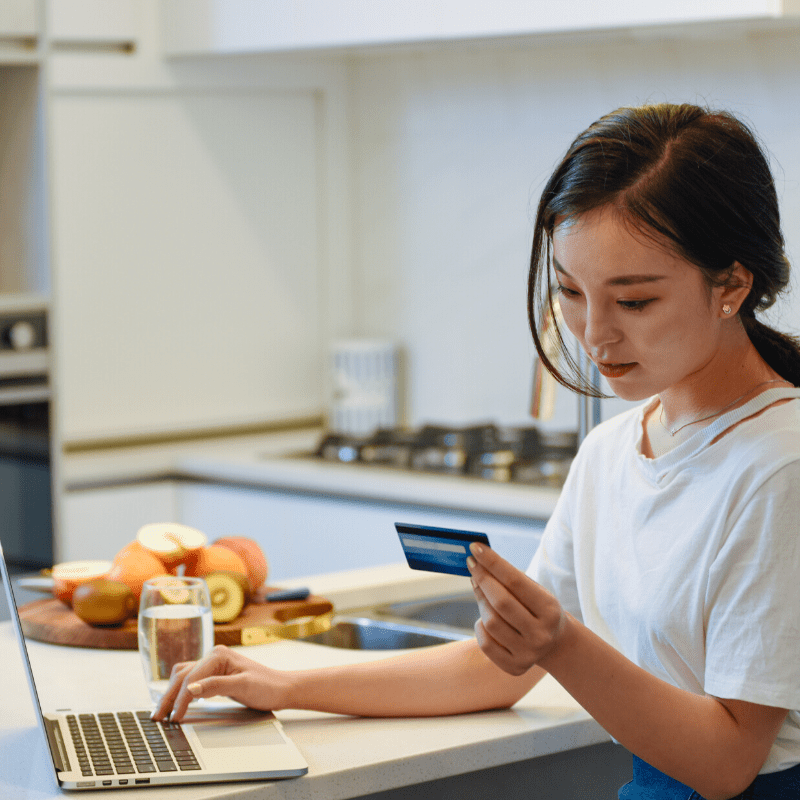 Woman online shopping on a laptop with credit card at her kitchen bench